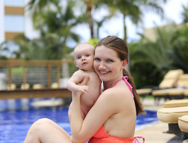 Beautiful young mother is holding baby girl outside near pool. Beautiful young mother is holding baby girl outside near fountain rock wall stock photos