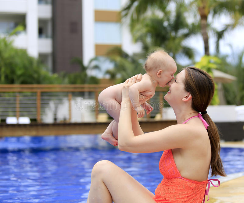 Beautiful young mother is holding baby girl outside near pool. Beautiful young mother is holding baby girl outside near fountain rock wall. Three months old royalty free stock image