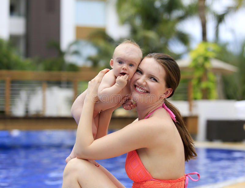Beautiful young mother is holding baby girl outside near pool. Beautiful young mother is holding baby girl outside near fountain rock wall. Three months old stock photo