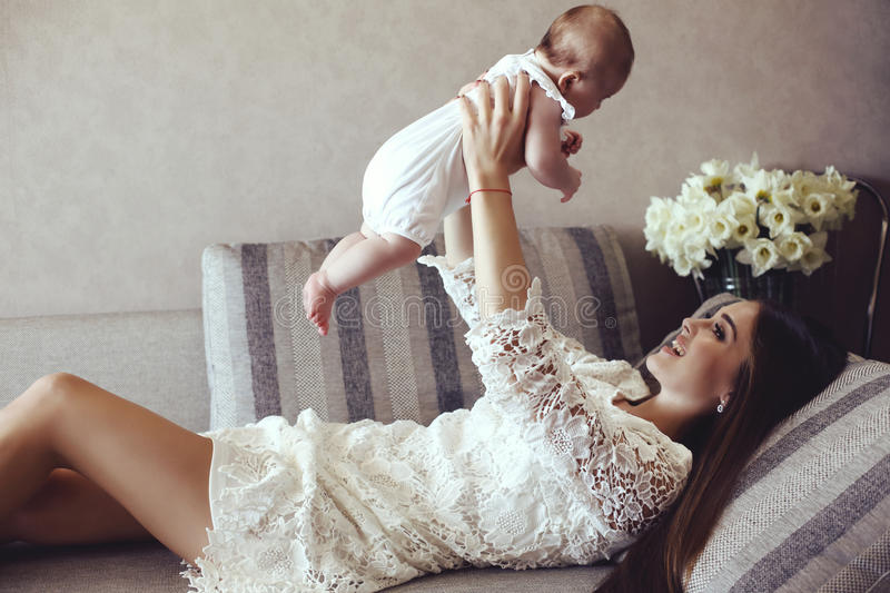 Beautiful young mother with long dark hair posing with her little adorable baby royalty free stock image