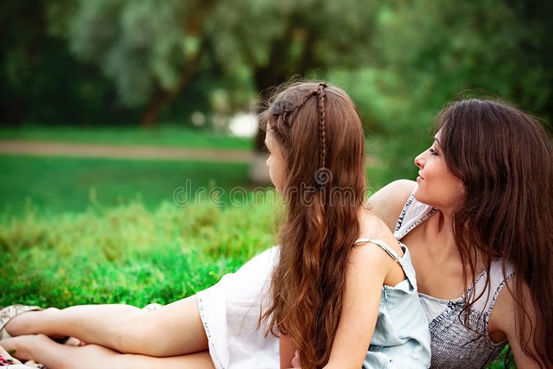 Beautiful young mother lying near her cute daughter and looking on summer green grass background in sunny day stock images