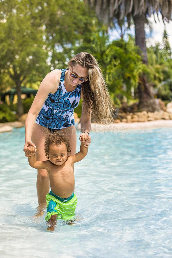 Beautiful young mother playing with her son on the pool. Smiling mixed race little boy playing in the water on vacation at a tropical resort. full length photo royalty free stock images