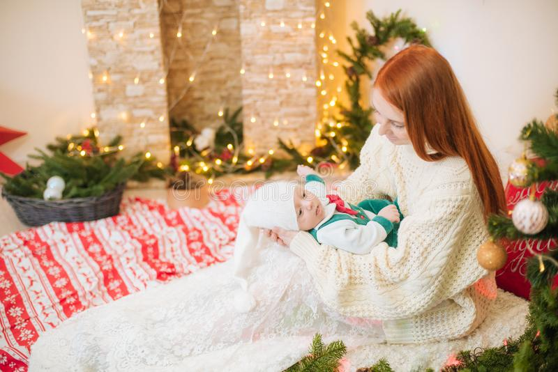 Beautiful young mother with red hair in a white knitted warm sweater holds a baby in her arms at home in a room decorated royalty free stock photo