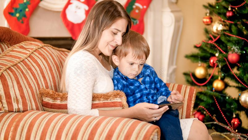 Beautiful young mother sitting in armchair with her little boy next to Christmas tree and watching video on smartphone royalty free stock images