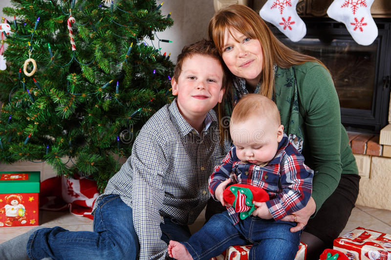 Beautiful young mother and two adorable sibling boys with Christ royalty free stock photos