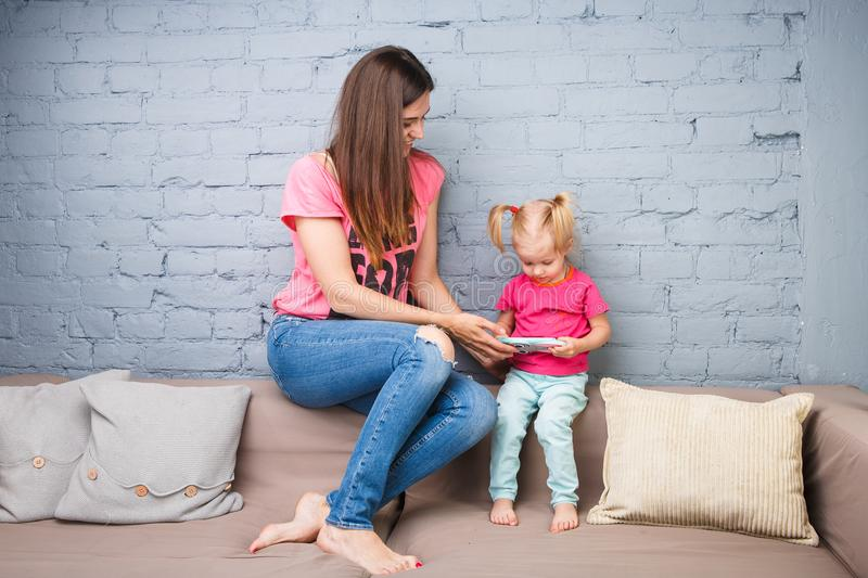 Beautiful young mother uses a smartphone to play with a two-year-old daughter sitting on the couch in the room Dressed in bright c stock photo