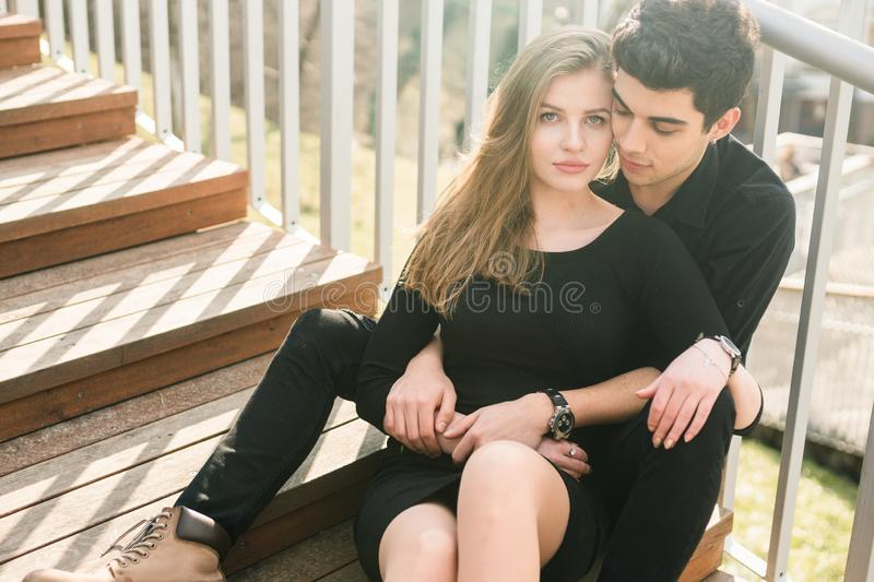 Beautiful young multiracial couple, student couple in love, sit wooden staircase in the city. Beautiful Turkish brunette guy hug a stock photos