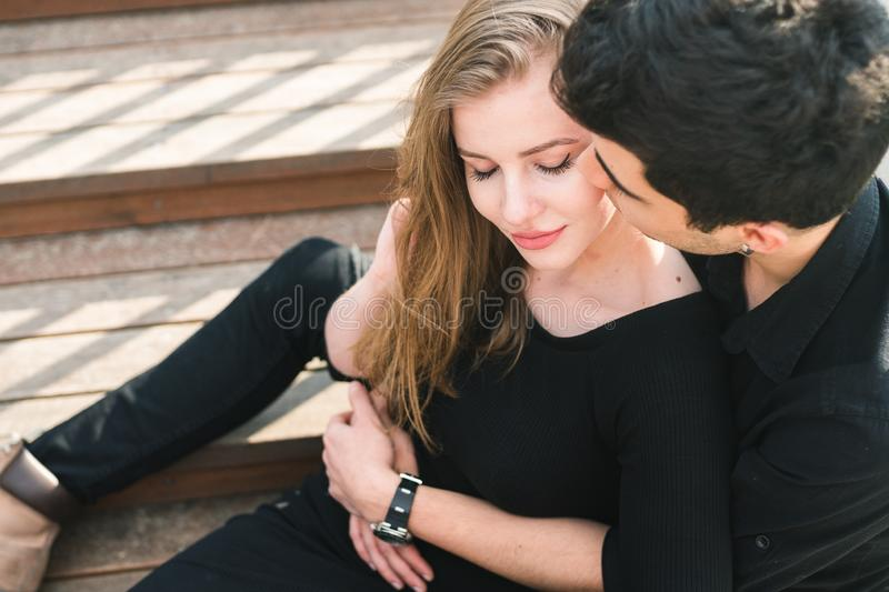 Beautiful young multiracial couple, student couple in love, sit wooden staircase in the city. Beautiful Turkish brunette guy hug a stock image