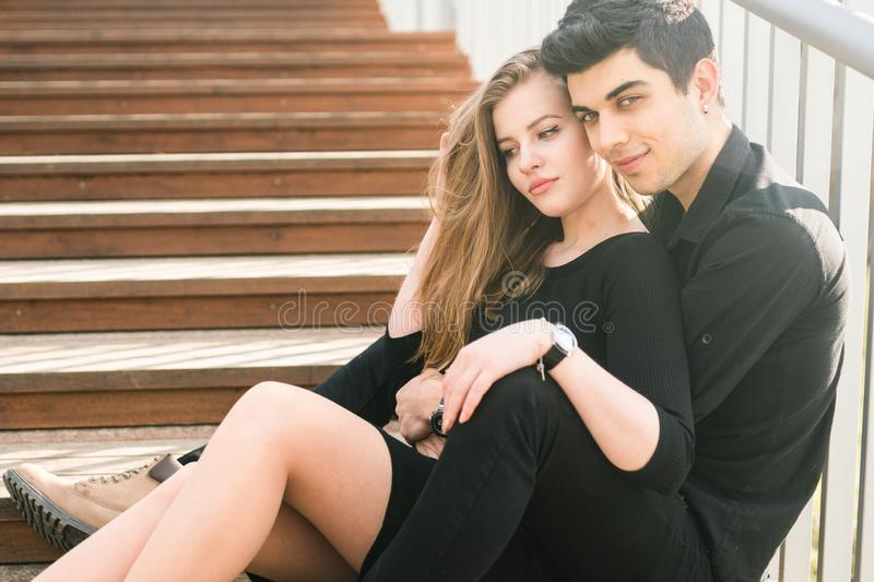 Beautiful young multiracial couple, student couple in love, sit wooden staircase in the city. Beautiful Turkish brunette guy hug a stock images