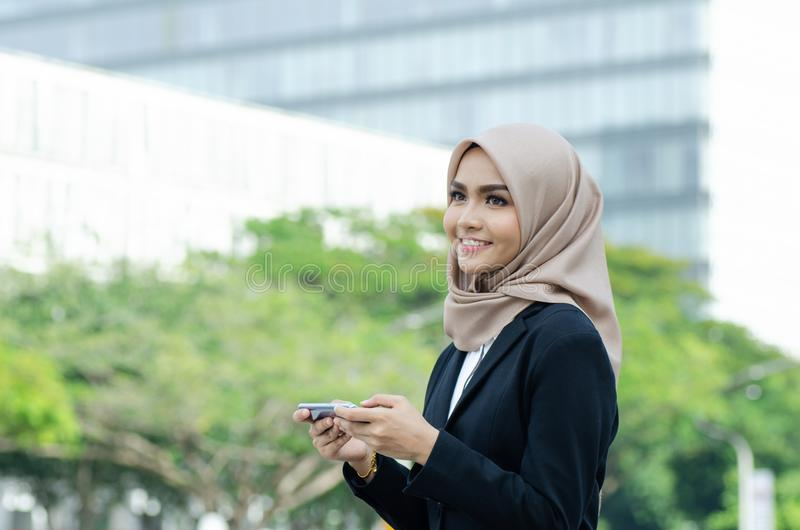 Beautiful young muslimah on black suit and hijab sitting outside using mobile phone. Shallow depth of field background royalty free stock photos