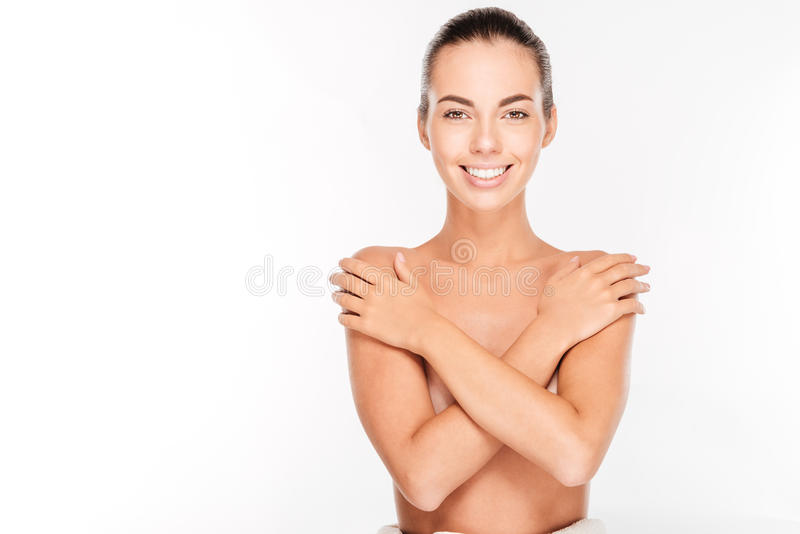 Beautiful young nude woman with arms crossed on her chest. Isolated on white background royalty free stock photos