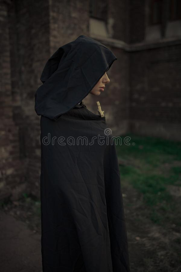 Beautiful young nun in black cassock and hooded cloak with cross. Beautiful young nun in black cassock and hooded cloak is standing and praying with cross in her royalty free stock photography