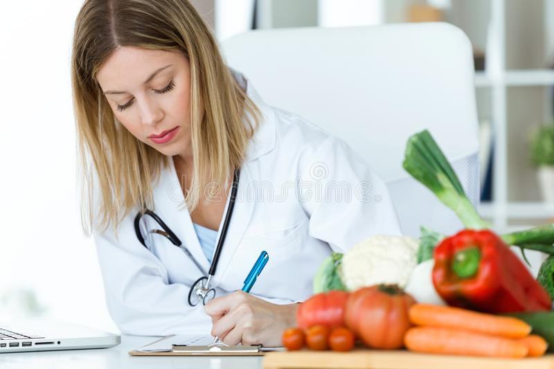 Beautiful young nutritionist working at desk and writing medical records over fresh fruit in the consultation. stock photo