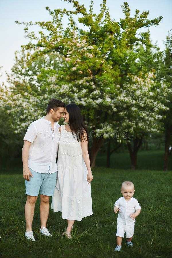 Beautiful young parents, stylish handsome man in shorts and shirt and brunette beauty in the white dress, and their cute royalty free stock photo