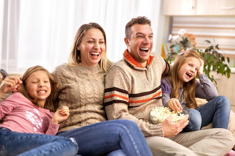 Beautiful young parents and their children are watching TV, eating popcorn and sitting on couch at home royalty free stock photo