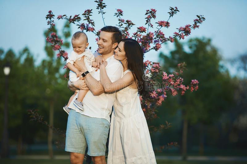 Beautiful young parents and their cute little son have fun at the green park royalty free stock photography