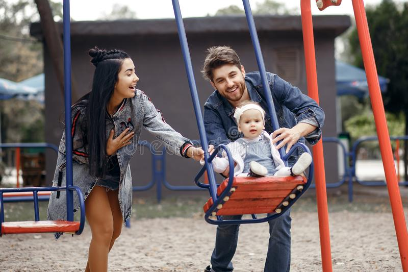 Beautiful young parents, walk with a child, swing him on a swing, have fun and enjoy each other, happy family for a walk stock images