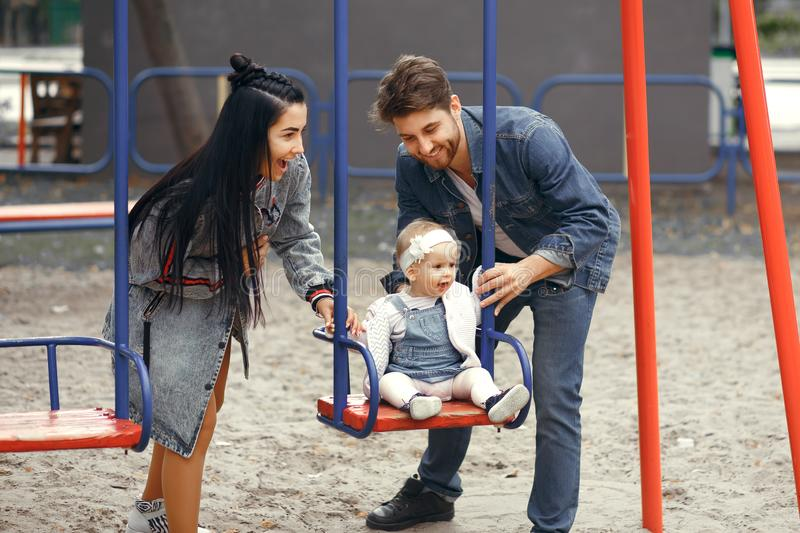 Beautiful young parents, walk with a child, swing him on a swing, have fun and enjoy each other, happy family for a walk stock photo