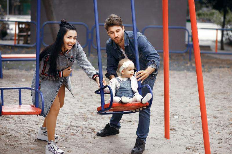 Beautiful young parents, walk with a child, swing him on a swing, have fun and enjoy each other, happy family for a walk stock photography