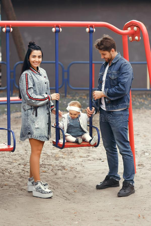 Beautiful young parents, walk with a child, swing him on a swing, have fun and enjoy each other, happy family for a walk royalty free stock image