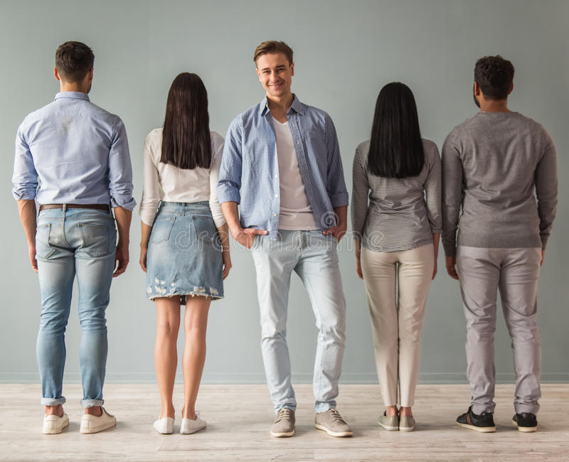 Beautiful young people. Full length portrait of beautiful young people standing in a row, their backs turned to camera, one guy is facing camera and smiling royalty free stock images