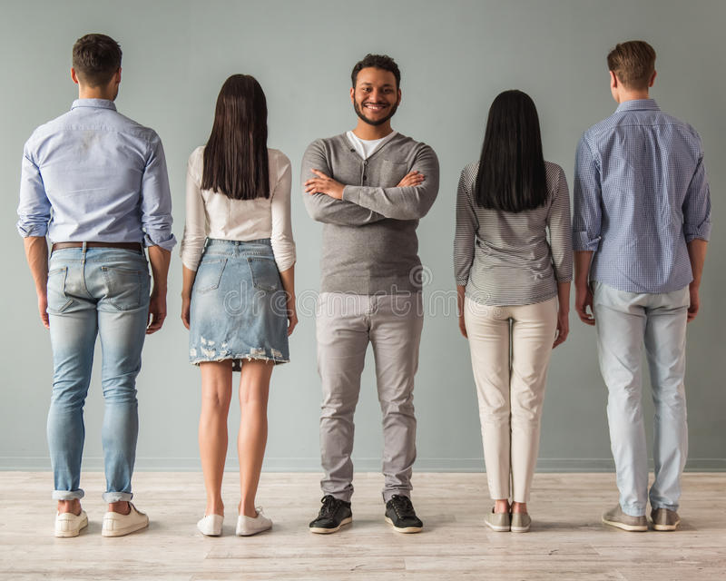 Beautiful young people. Full length portrait of beautiful young people standing in a row, their backs turned to camera, one guy is facing camera and smiling royalty free stock photos