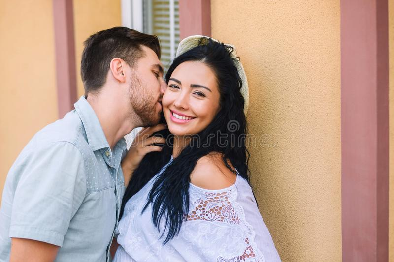 Beautiful, young people kiss, girl is happy, beautiful warm evening, woman in a hat royalty free stock photography