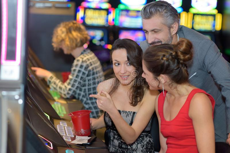 Beautiful young people near slot machine in casino royalty free stock photography