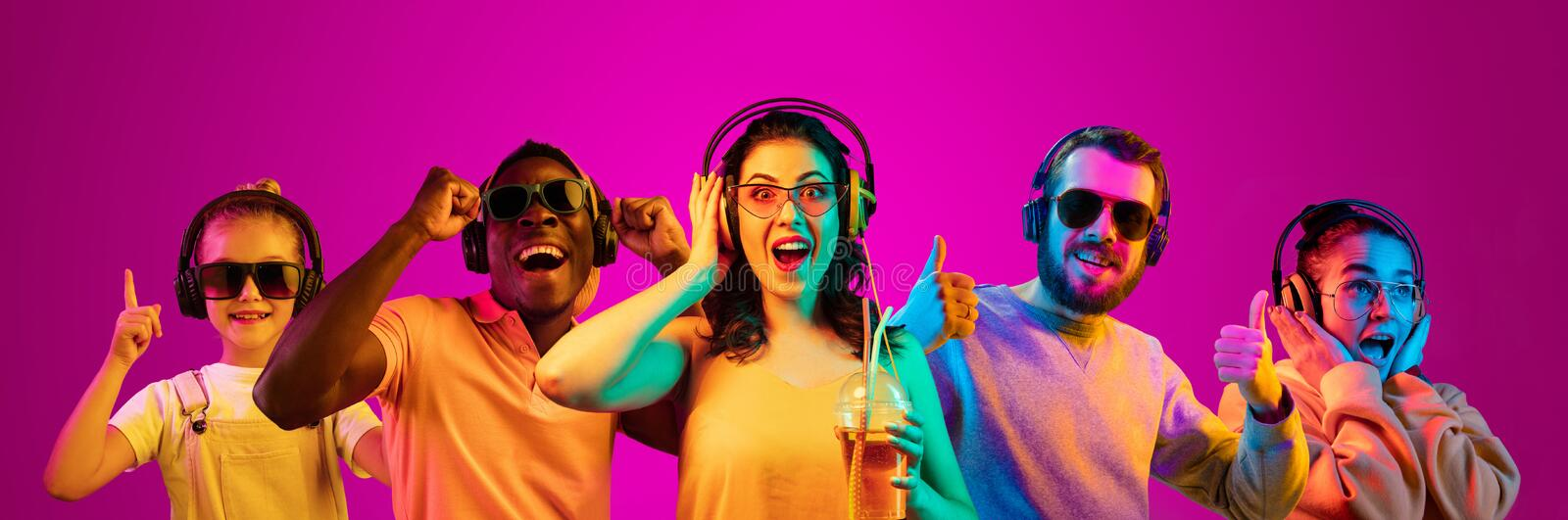 Beautiful young people in neon light isolated on pink studio background stock images