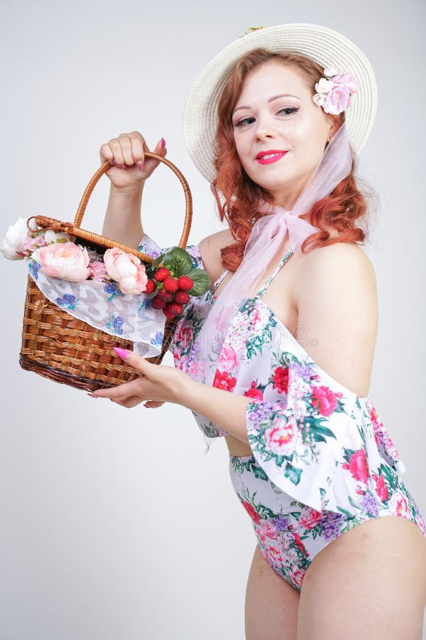 Beautiful young pin up caucasian girl in romantic fashionable straw hat, vintage swimsuit with flowers and retro wicker basket pos royalty free stock photography