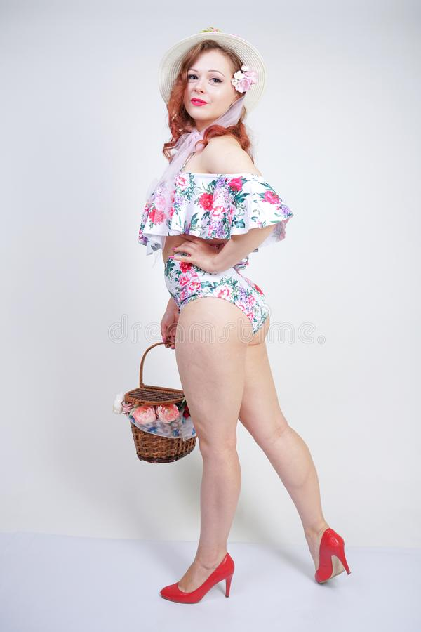 Beautiful young pin up caucasian girl in romantic fashionable straw hat, vintage swimsuit with flowers and retro wicker basket pos stock photography