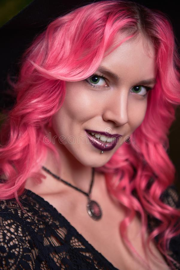 Beautiful young pink-haired witch. Close-up portrait of smiling young girl. Beautiful young pink-haired witch. Close-up portrait of a smiling young girl stock image
