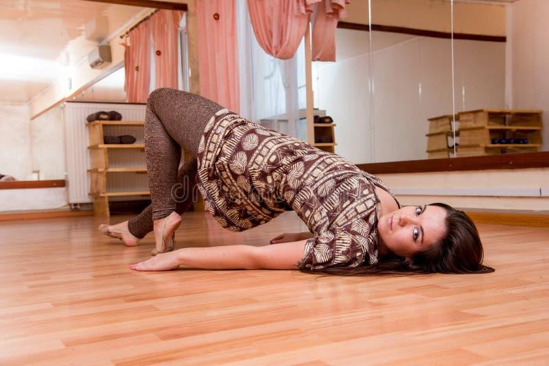 Beautiful, young, plastic flexible girl doing yoga dance in the dance floor royalty free stock image