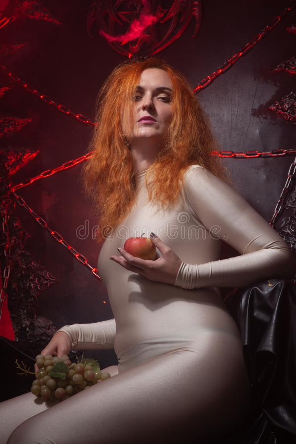Beautiful Young plus size red hair woman as seductive temptress. halloween portrait of evil curvy woman in skin color stock photo