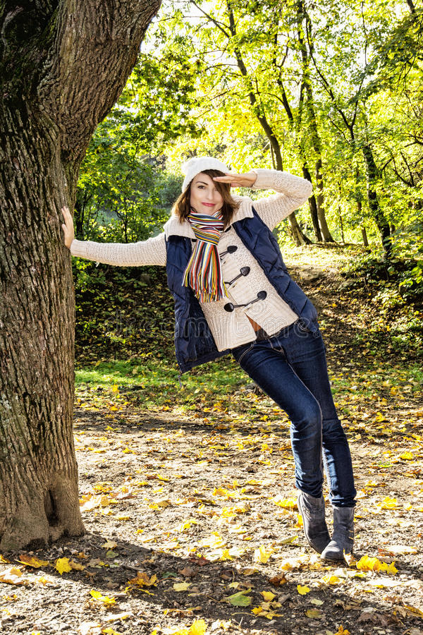 Beautiful young positive woman saluting under the beech tree in royalty free stock image