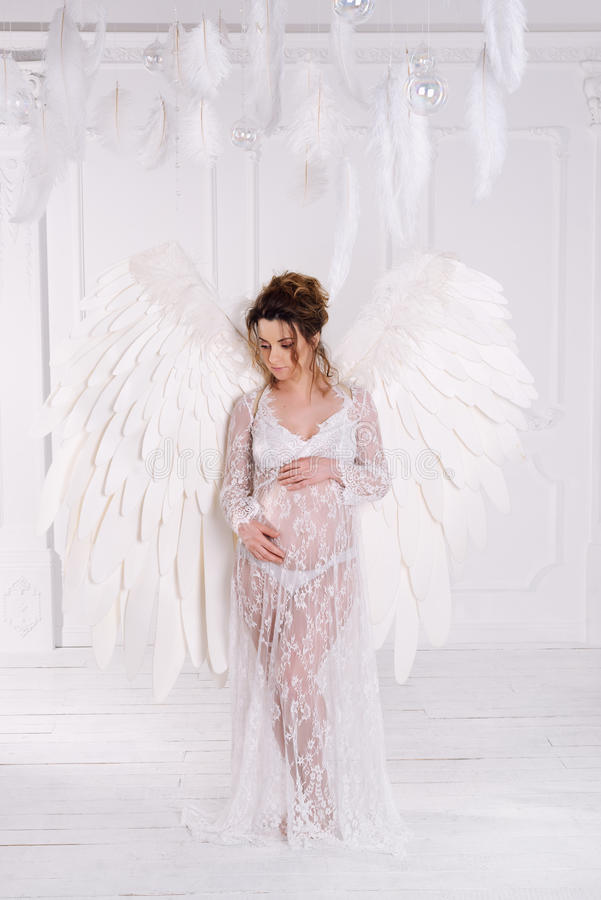 Beautiful young pregnant girl with big angel wings stock photo