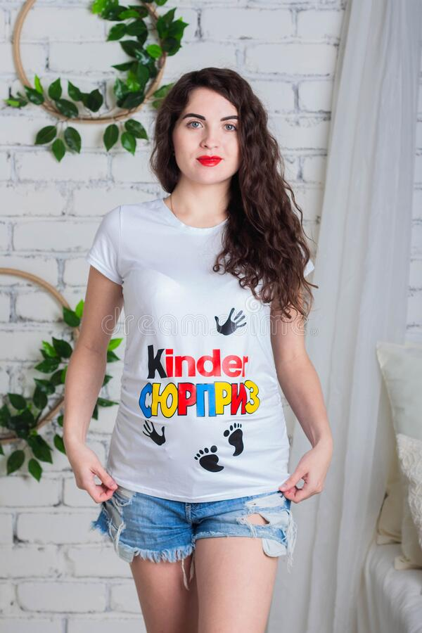 Beautiful young pregnant woman with curly hair in a t-shirt with a Kinder Surprise print poses in the Studio stock images