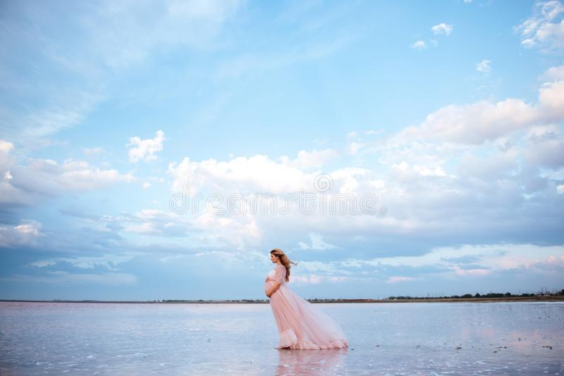 Beautiful young pregnant woman enjoying the sun on pink lake. Beautiful young pregnant woman enjoying the sun on the beach, pink lake royalty free stock images