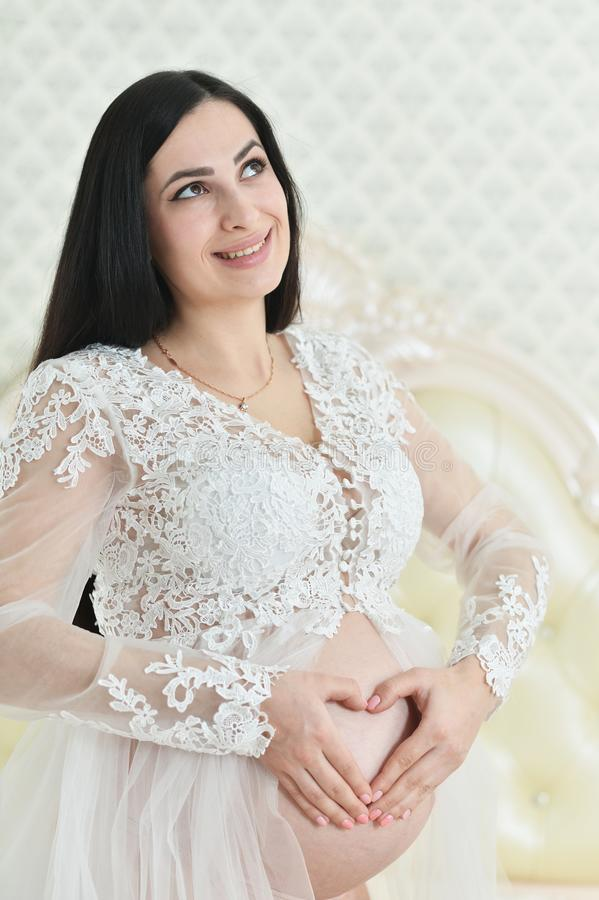 Portrait of beautiful young pregnant woman making heart sign stock photography