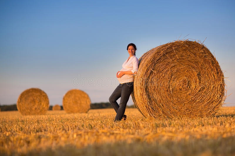 Beautiful young pregnant woman relaxing in a hay bales field royalty free stock photo
