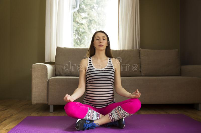 Beautiful young pregnant woman sitting in lotus position on yoga royalty free stock images