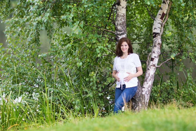 Beautiful young pregnant woman walking next to river royalty free stock images