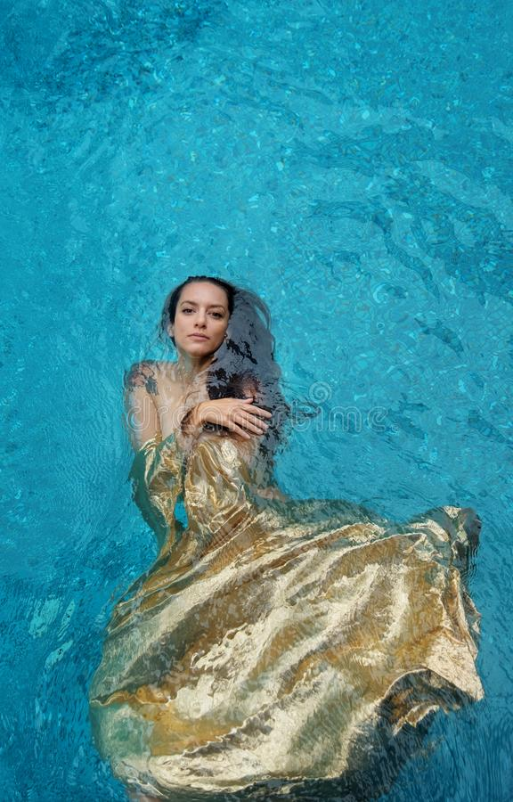 Beautiful young proud woman in golden dress, evening dress floating weightlessly elegant floating in the water in the pool dark royalty free stock images