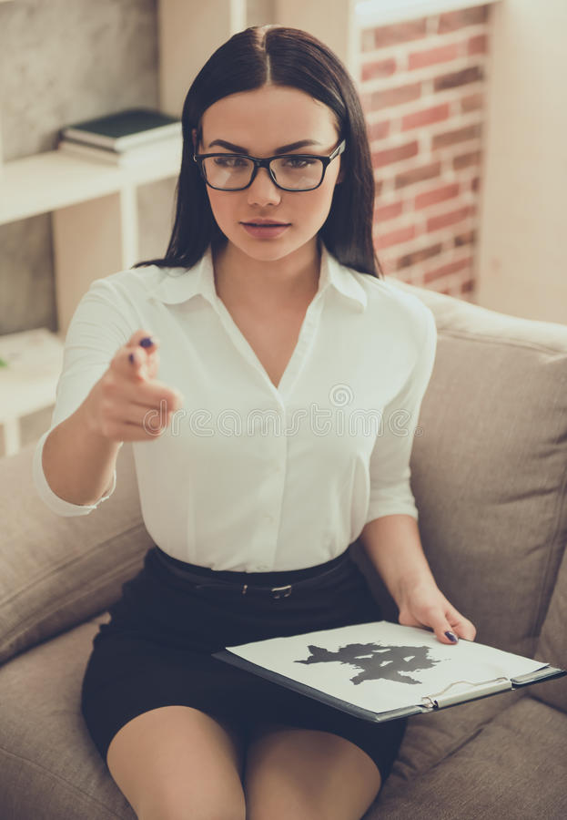 Beautiful young psychologist. Beautiful female psychologist is holding the Ink blot test, pointing and looking at camera while sitting in her office royalty free stock images
