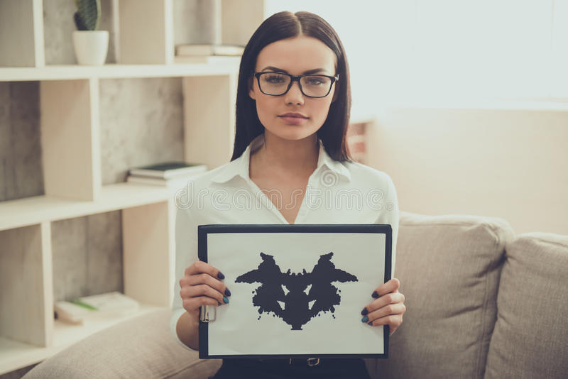 Beautiful young psychologist. Beautiful female psychologist is showing the Ink blot test and looking at camera while sitting in her office royalty free stock image
