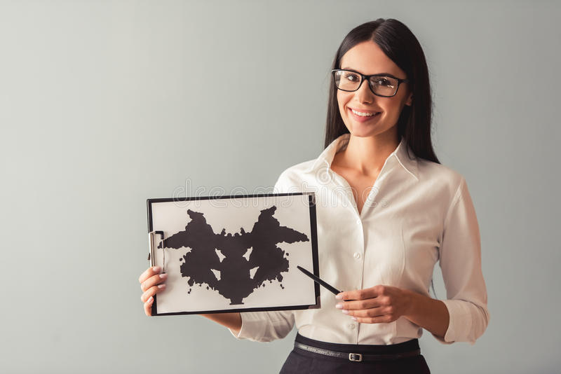 Beautiful young psychotherapist. Is showing the Ink blot test, looking at camera and smiling, on gray background stock photography