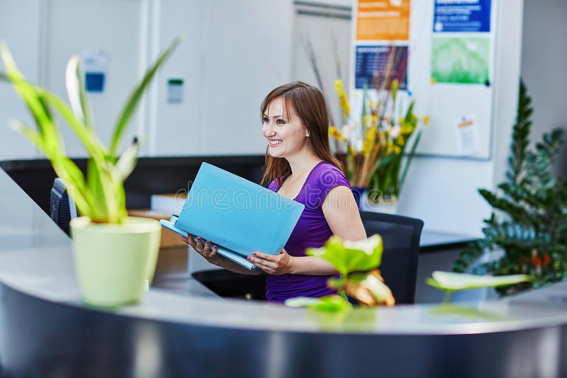 Beautiful young receptionist at work. Business, communication and call center concept - beautiful young receptionist at work royalty free stock photography