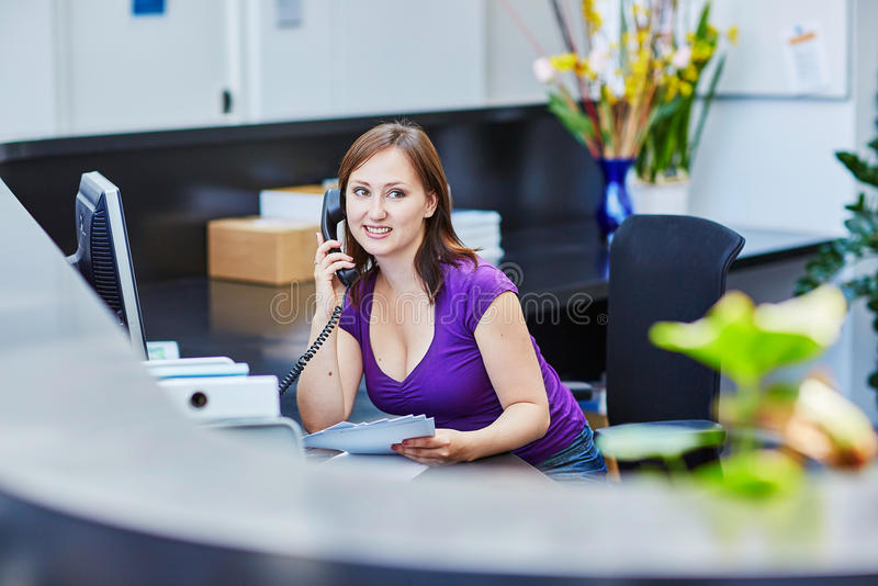 Beautiful young receptionist at work. Business, communication and call center concept - beautiful young receptionist at work royalty free stock images