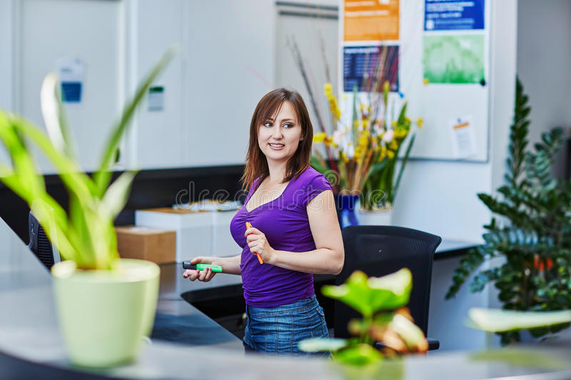 Beautiful young receptionist at work. Business, communication and call center concept - beautiful young receptionist at work stock image