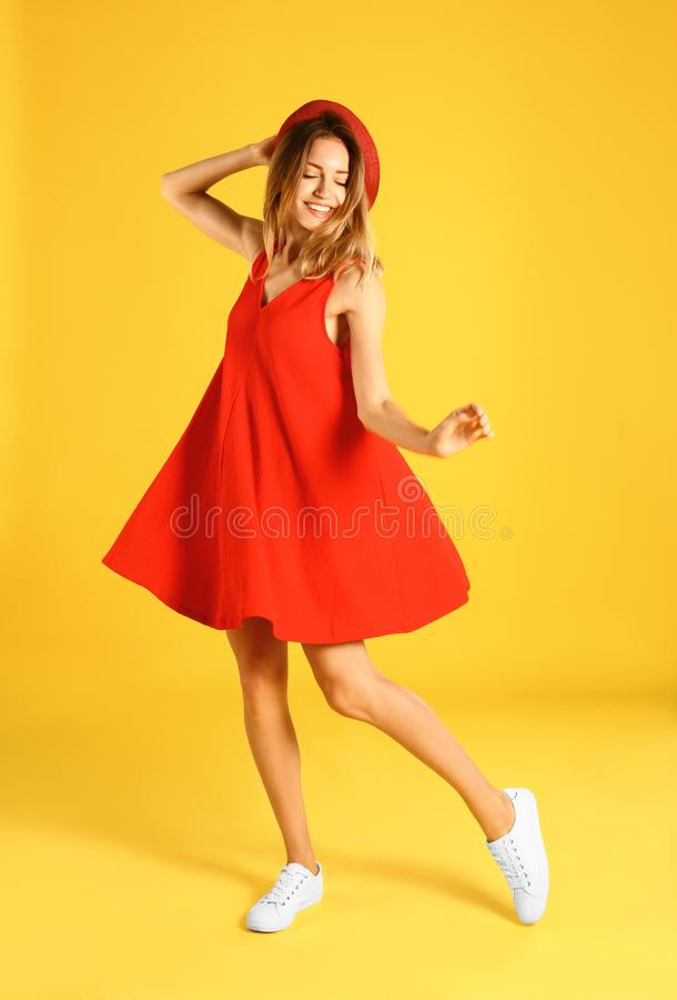 Beautiful young  in red dress dancing on yellow background royalty free stock photo